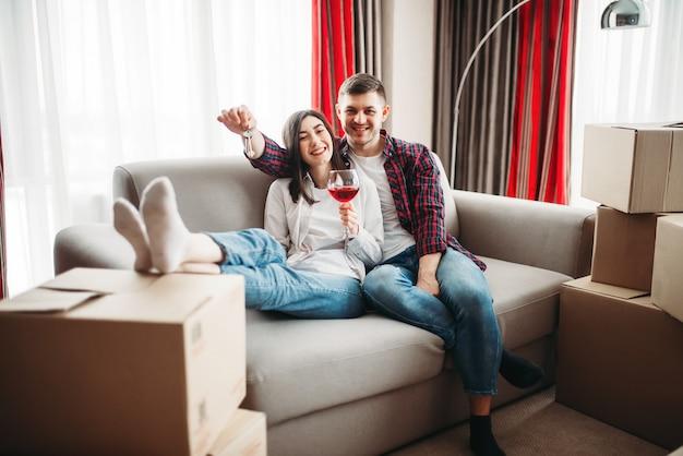 행복한 커플은 레드 와인을 마시고 새 집으로 이사를 축하합니다. 아파트 축하 행사로 이전