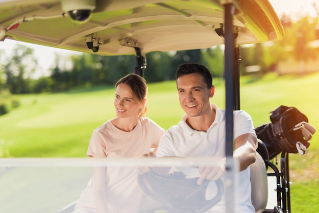 Happy couple driving golf car carrying golf bats.