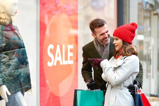 Счастливая пара во время покупок в окне