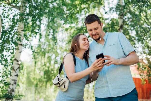 Happy couple in earphones messaging on mobile