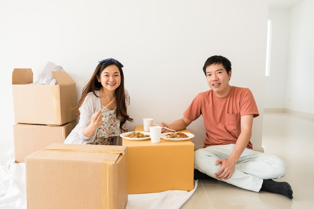 Happy couple eat noodle on carboard box at new house