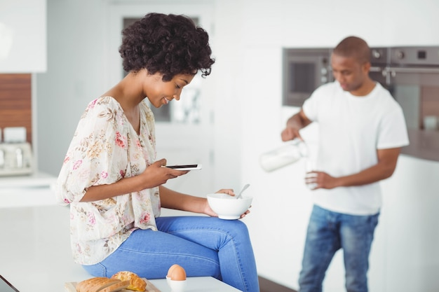 Happy couple eating breakfast and using smartphone in the kitchen at home
