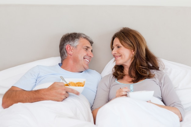 Happy couple eating cereals in bed
