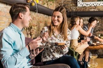 プレート上のピザのスライスを食べて幸せなカップル