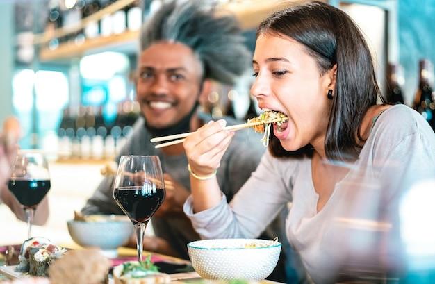 寿司バーレストランでポークボウルを食べる幸せなカップル