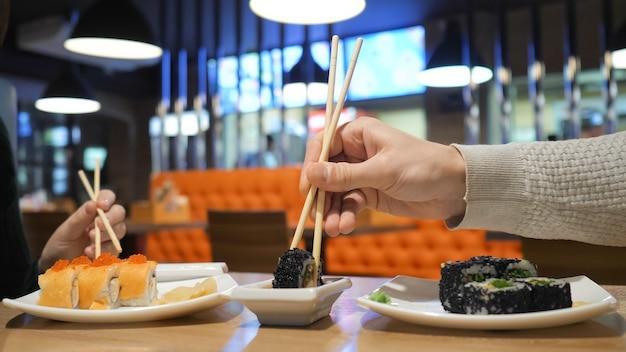 日本のレストラン、寿司バーで巻き寿司を食べる幸せなカップル。日本食、ダイエット、ダイエット。