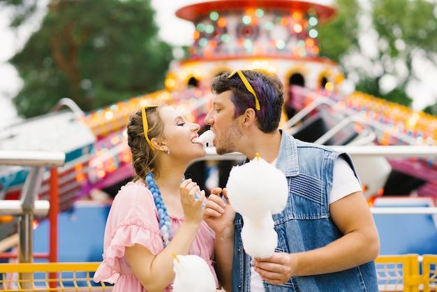 Счастливая пара ест сладкое и целуется в летнем парке