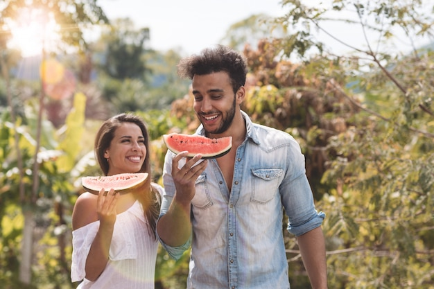 Happy couple eating water melon together cheerful