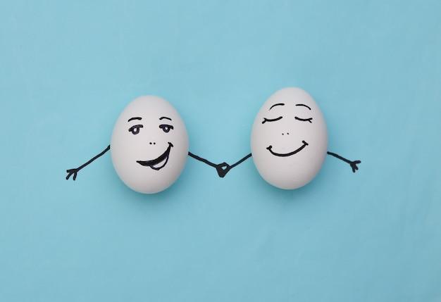 Счастливая пара яиц с рисованными лицами на синем фоне