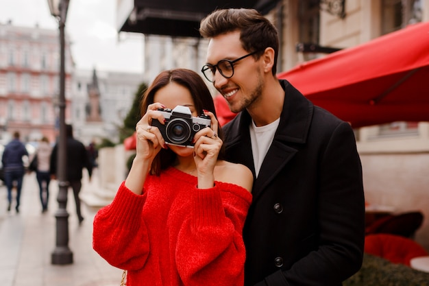 Happy couple embarrassing and posing on the street on holiday. romantic mood. lovely brunette woman holding film camera.