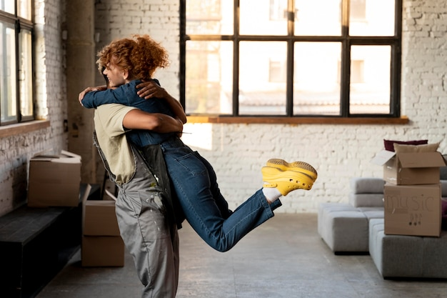 Happy couple embracing after moving in together in a new home