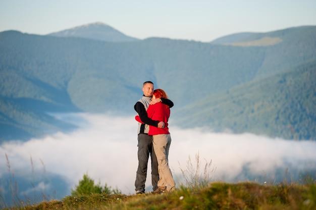 Happy couple embracing against beautiful mountain landscape