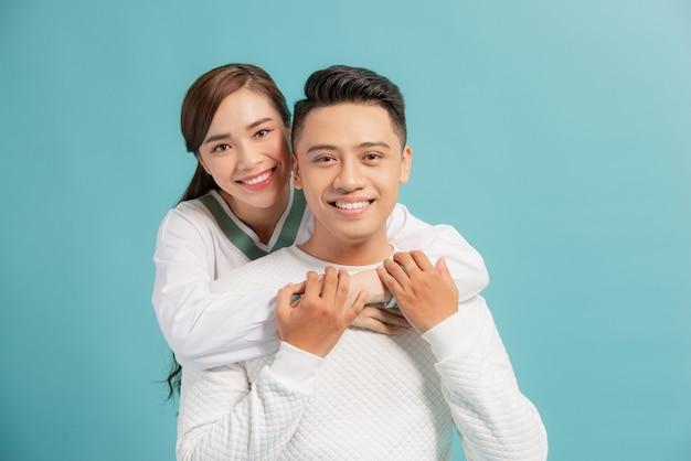 Счастливая пара, обнимая и глядя в камеру на синем