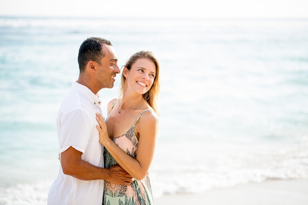 Happy couple embracing on beach in summer