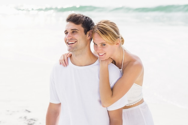 Happy couple embracing on the beach