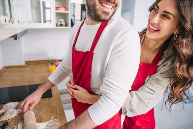 Happy couple embracing and cooking together