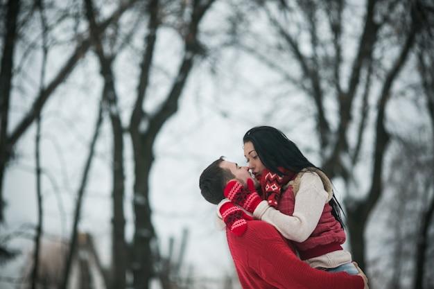 Счастливая пара, охватывающей в зимних лесах