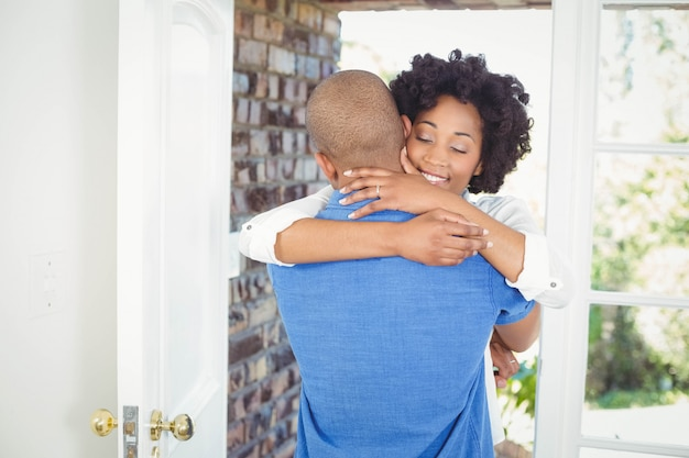 Happy couple embracing in their house