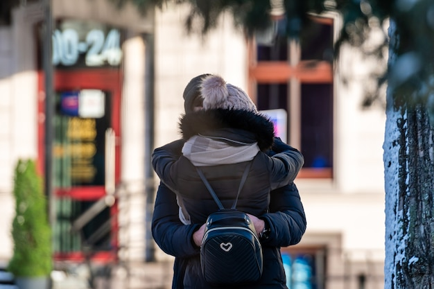Happy couple embracing while standing together on a street in the city