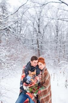 행복한 커플은 눈 덮인 나무에서 강아지와 함께 진정 산책을 즐길 수