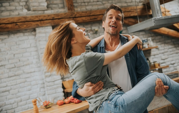 Happy couple enjoy each other in the modern kitchen while man holding woman on hands