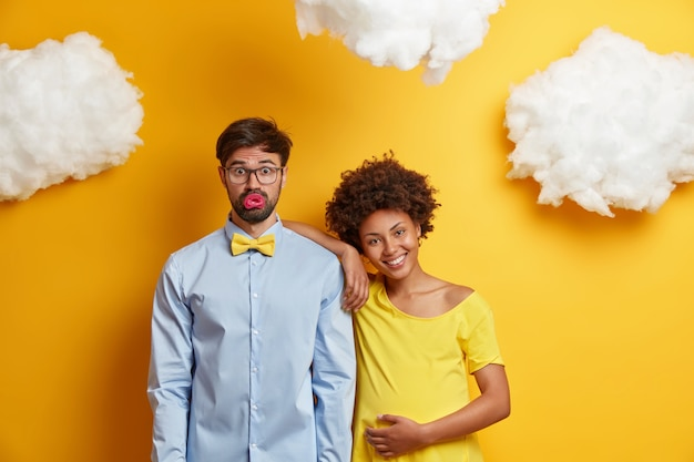 幸せなカップルは妊娠の瞬間を楽しんで、すぐに両親になることを嬉しく思います。嬉しい妊婦は夫の肩に寄りかかって、将来の赤ちゃんの名前を考え、黄色い壁に一緒にポーズをとる