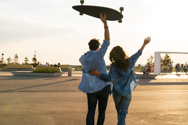 幸せなカップルは、腕を上げて日没の抱擁を楽しむロングボードの幸福と自由の概念を保持します