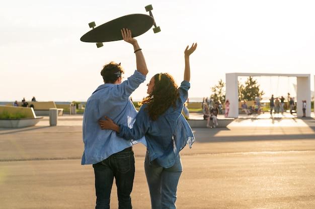 행복한 커플은 팔을 들고 롱보드 행복과 자유 개념을 잡고 일몰 포옹을 즐깁니다.