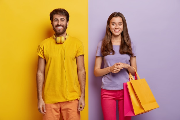 Happy couple enjoy weekend, make purchasing, hold shoppings bags, wears bright outfit, being in high spirit