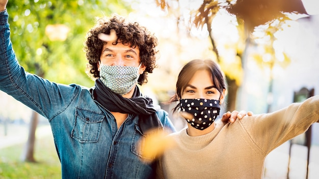 フェイスマスクを身に着けている秋の時間を屋外で楽しんでいる幸せなカップル-男の顔に焦点を当てる