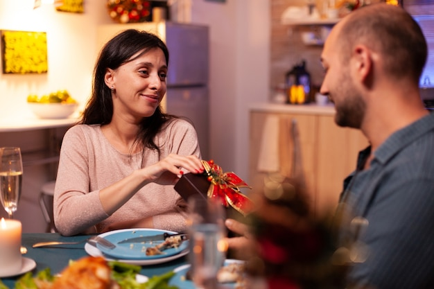 Happy couple enjoying christmas holiday surprising with xmas present with ribbon on it