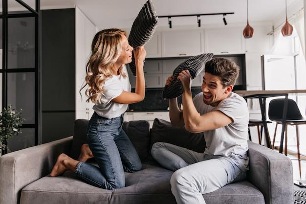 베개 싸움을 즐기는 행복 한 커플. 거실에서 남자 친구와 놀고 다행 소녀.