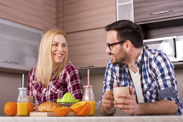 부엌에서 갓 짜낸 오렌지 주스로 아침 식사를 즐기는 행복한 커플