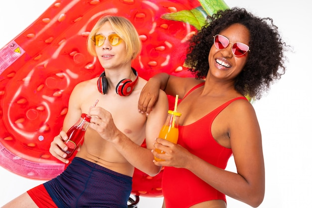 Happy couple european guy and african girl in swimsuits with sunglasses and headphones with cocktails in their hands