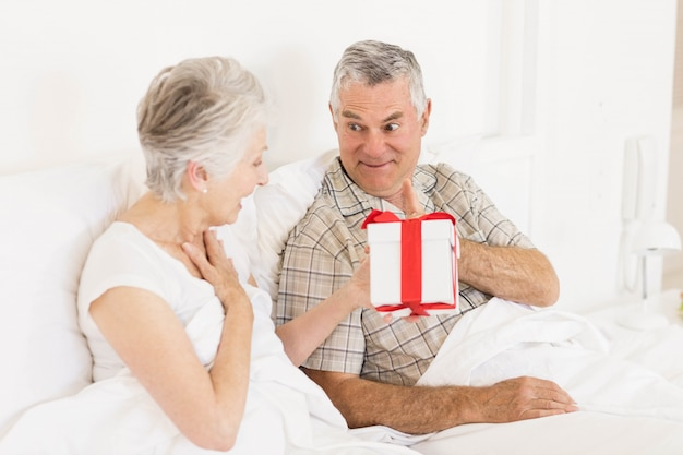 Happy couple exchanging gift at bed