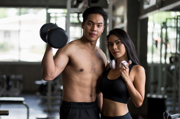 Happy couple exercise dumbbell in fitness