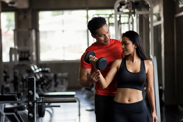 Happy couple exercise dumbbell in gym