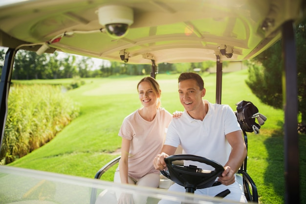 Happy couple family is driving golf car on course.