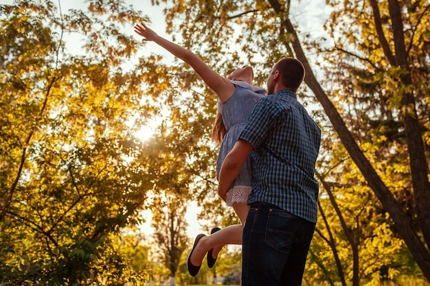 Happy couple feeling free in spring park. man holds his girlfriend in hands at sunset