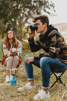 Happy couple in the forest drinking coffee