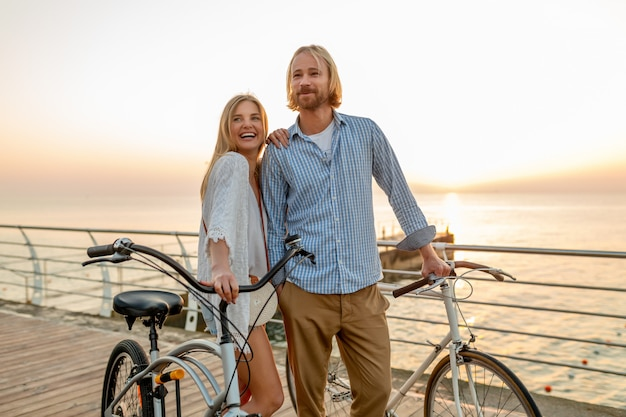 Happy couple of friends traveling in summer on bicycles