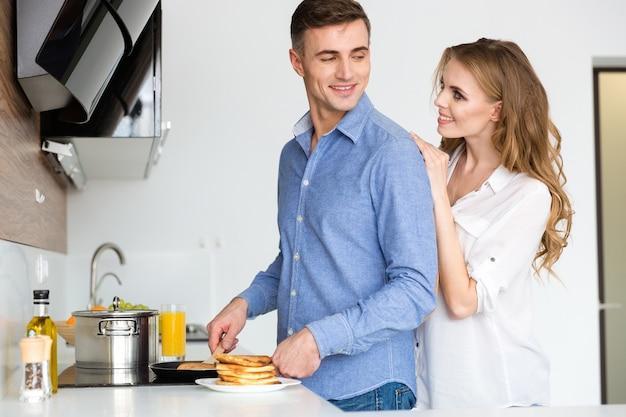幸せなカップルがパンケーキを揚げて、自宅の台所でいちゃつく