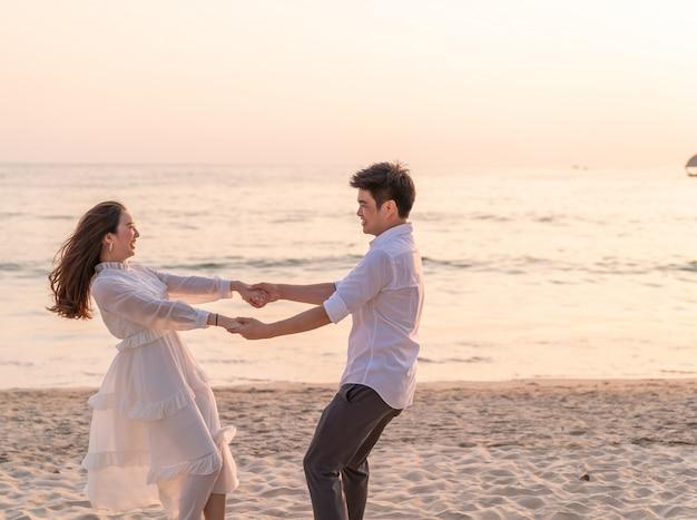 夏の熱帯の砂浜に新婚旅行に行く幸せなカップル