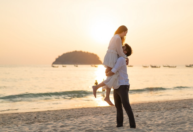 Happy couple going honeymoon travel on tropical sand beach in summer