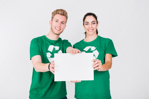 Happy couple in green t-shirt holding blank white placard