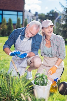 Happy couple. happy loving couple taking care of their garden bed outside the house while planting new flowers