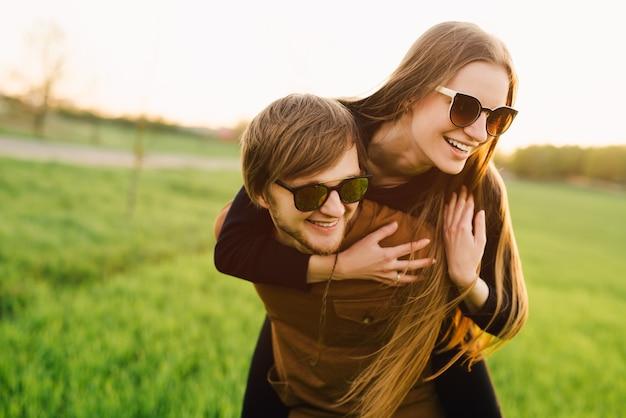 Счастливая пара веселится на открытом воздухе. молодая семья, прогулки на свежем воздухе в летнем поле
