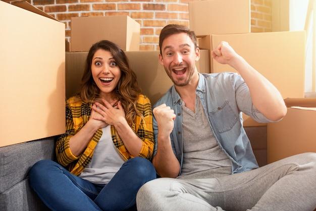 행복한 커플은 새 집을 찾았고 모든 패키지를 준비해야합니다. 성공, 변화, 긍정 및 미래의 개념