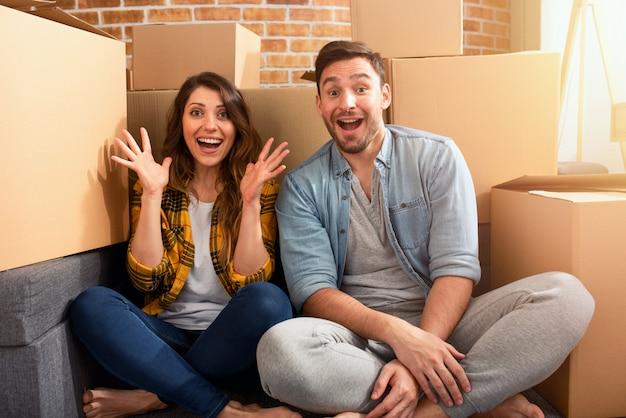幸せなカップルが新しい家を見つけて、すべてのパッケージを手配する必要があります。成功、変化、積極性、そして未来のコンセプト