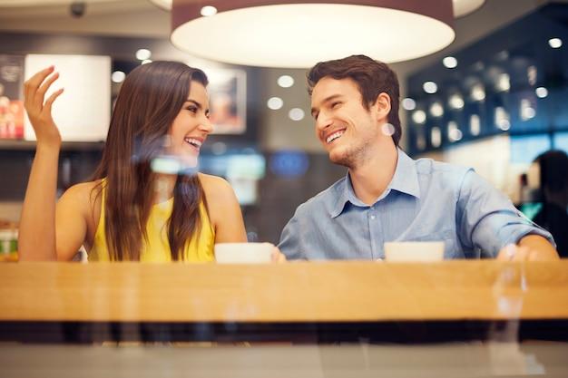 幸せなカップルはカフェで楽しんでいます
